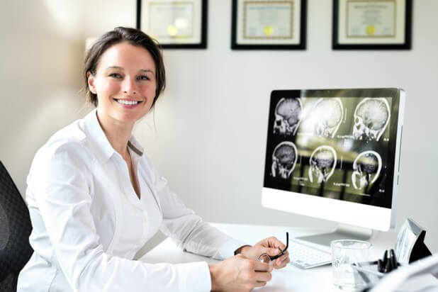 woman neurosurgeon smiling at her desk